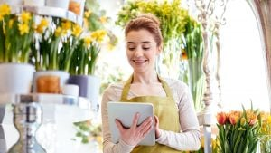 A florist in her shop holding up an iPad to check orders and stock levels.