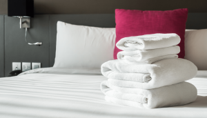 Stack of white towels on a neatly made bed in a hotel