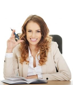 A recruitment consultant sitting at a desk smiling
