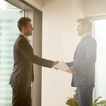 Two smartly dressed professionals shaking hands and smiling at one another in an office environment
