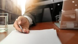 Close up of a businessman holding a pen against paper next to a laptop