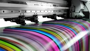 A commercial printer in action, printing a large scale image featuring bright colours