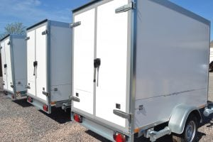 A fleet of white refrigerated trailers lined up, sold by refrigeration Trailers