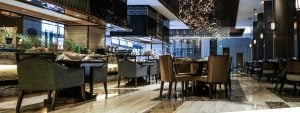 A newly fitted out restaurant with a bar featuring fabric chairs, marble floor and elegant decorations hanging from the ceiling