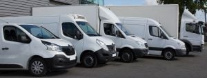 A fleet of white commercial vehicles lined up outside a distribution centre